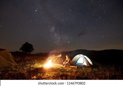 Young woman traveller enjoying at night camping near burning campfire, illuminated tourist tent, mountain bike under beautiful evening sky full of stars. Outdoor activity and tourism concept