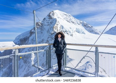 Young woman traveller enjoying the view of rock cliff Jungfrau peak view from Jungfraujoch, Top of Europe in Switzerland