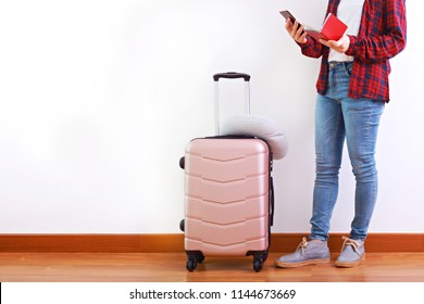 Young woman traveller with light pink luggage, using mobile phone, ready for her holidays. With copy space