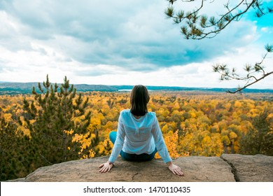 Young woman traveller sitting on a steep rock, admiring panoramic view of autumn forest in Algonquin Provincial Park, Ontario, Canada. Rear view