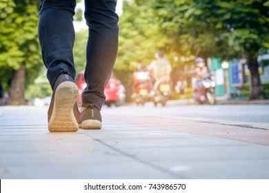 Young Woman traveller walking on the road, female legs exercise on footpath in morning sunlight , jean and sneaker shoes. Alone travel concept