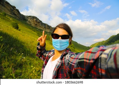 Young woman traveller wearing face mask outside at the nature and taking selfie at the mountains in Caucasus Russia. - Shutterstock ID 1803662698