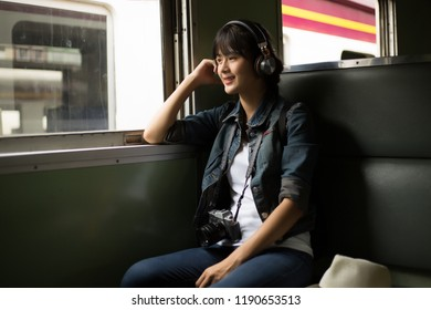 Young woman travels by train.  sad smiling looking to the right side window on the Train. copy space,,travel, backpack concept