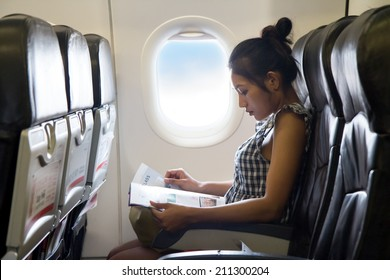 Young woman travels in a chair of the airplane.  Passengers reads a magazine in the window of the aircraft. Enjoy - entertainment on board of flying air plane.
