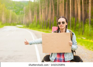 Young woman travels hitchhiking with a cardboard sign in her hands. Space for text