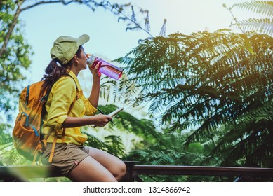 The young woman travels recording and studying the nature of the forest. She is sitting, relaxing and drinking water.