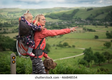 A young woman trekking with baby in a baby carrier and her dog, pointing at something in the landscape. Hiking activity with child and dog on family summer vacation, weekend nature tour