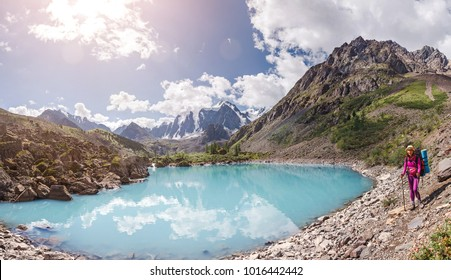 Young woman trekking at mountain trail above beautiful blue color lake