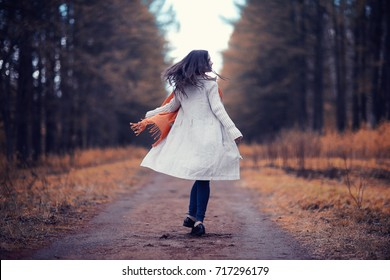 young woman in a trench coat walks in autumn park