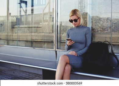 Young woman with trendy look reading information on mobile phone while waiting outdoors on a her taxi, stylish female tourist using cell telephone for view city map on-line while sitting on a bus stop
