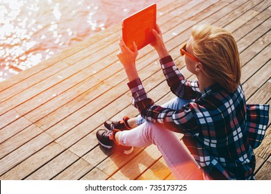 Young woman with trendy look shoot video on digital tablet while sitting on a wooden pier in summer sunny day, female hipster photographing on touch pad amazing landscape during her vacation holidays