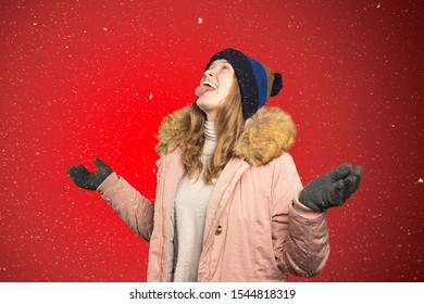 a young woman tries to catch snowflakes with her mouth