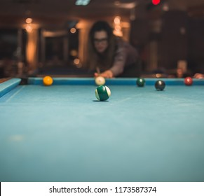 young woman tries hard to win billiard game. she struggles to hit the right ball on pool table