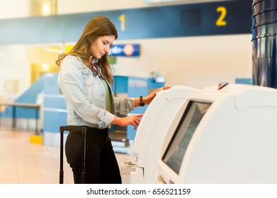 Young woman with trolley bag using self check-in machine in airport.