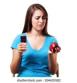 young woman trying decide between and healthy snack and sweets