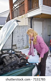 Young woman trying to fix the car