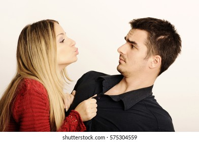 Young woman trying to kiss a young man