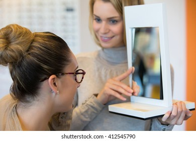 Young woman trying on glasses