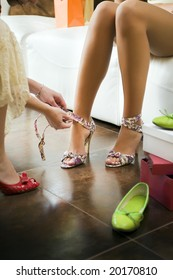 Young woman trying on high heel shoes, woman tying straps of shoes