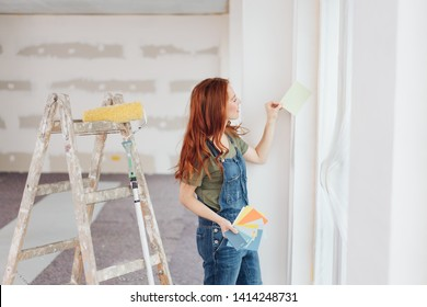 Young woman trying out color swatches for paint holding them up against a newly painted white wall as she does DIY renovations at home