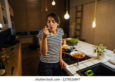 Young woman trying out healthy meal in home kitchen.Making dinner on kitchen island standing by induction hob.Preparing fresh vegetables,enjoying spice aromas.Eating in.Passion for cooking.Dieting