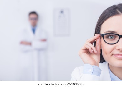 Young woman trying oval shape black glasses in optician's store