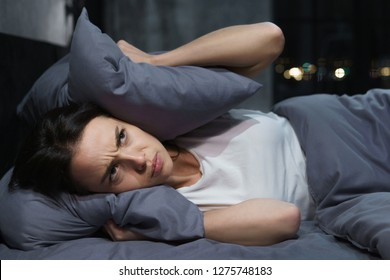 Young woman trying to sleep but disturbed by noisy neighbors and covering ears with pillows