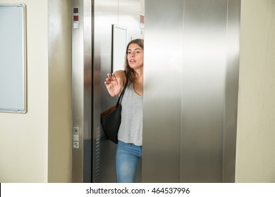 Young Woman Trying To Stop Door In Elevator