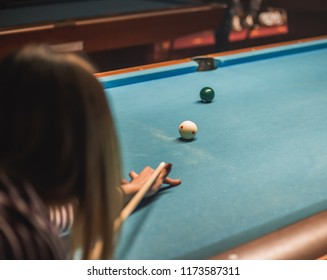 young woman trying to win a billiards game