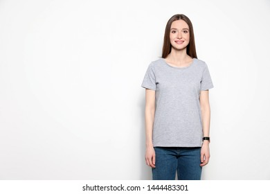 Young woman in t-shirt on light background. Mock up for design