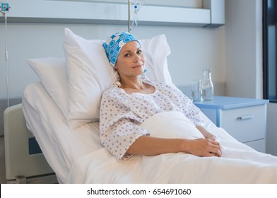 Young woman with tumor lying on hospital bed and looking at camera. Hopeful woman recovering from medical disease. Smiling woman with bandana on head resting in hospital ward after chemotherapy.