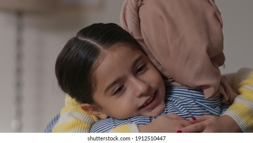 Young woman in turban and her cute little daughter are hugging and smiling.