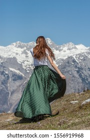 young woman turning in green dotted skirt fluttering in the wind
