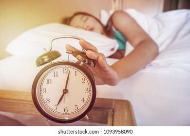 Young woman turns off the alarm clock waking up at morning in bedroom