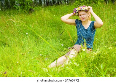 Young woman twining a  wreath on the meadow