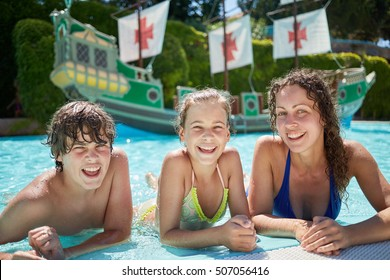 Young woman and two children lie on edge of swimming pool and smile.