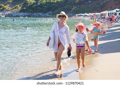 young woman with two children walking on sandy beach on the sea coast