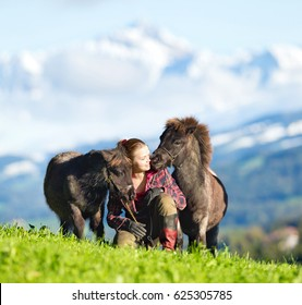 Young woman with two mini Shetland ponies. Two horses and beautiful lady outdoor on mountain background. Horse rider.