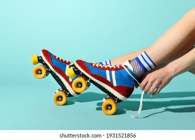 Young woman tying the laces on her red and blue rollerskates with colorful yellow wheels in a close up side view of her feet and hands over a blue background with copyspace