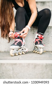 Young woman tying rollerskates