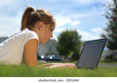 A young woman types on her computer in the grass.