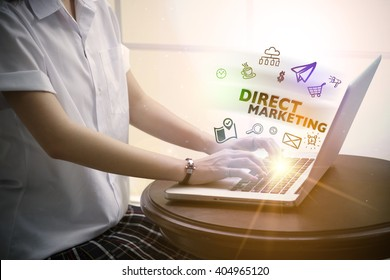 young woman typing DIRECT MARKETING  over notebook computer with and icon , business concept
