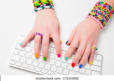 Young woman typing on a computer keyboard wearing loom bracelets on her hands. Close up. Young fashion concept