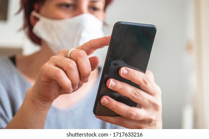 Young woman typing on mobile phone while wearing protective mask