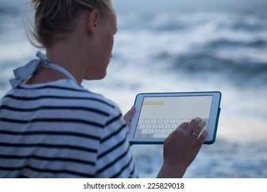 Young woman typing on touchpad sitting alone on the beach. Blurry sea in background