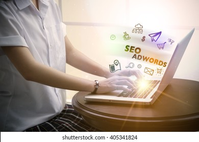 young woman typing SEO ADWORDS over notebook computer with and icon , business concept , business idea , strategy concept