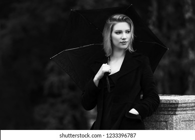Young woman with umbrella walking in city street Stylish fashion model wearing classic black coat