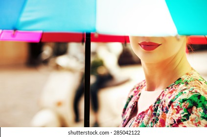 Young woman under an colorful umbrella