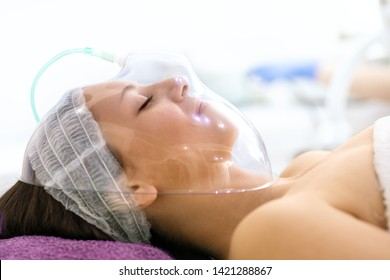 Young woman under cosmetic oxygen mask in cosmetic center. Facial treatment for nutrition, hydration and regeneration skin