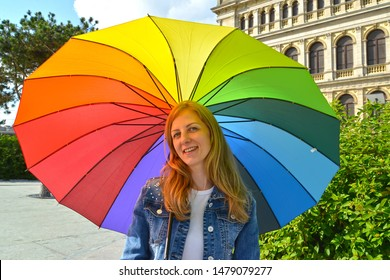The young woman under an iridescent umbrella in summer day